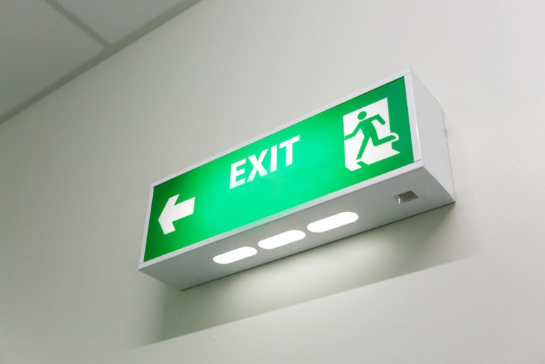 Emergency exit sign, representing health and safety.