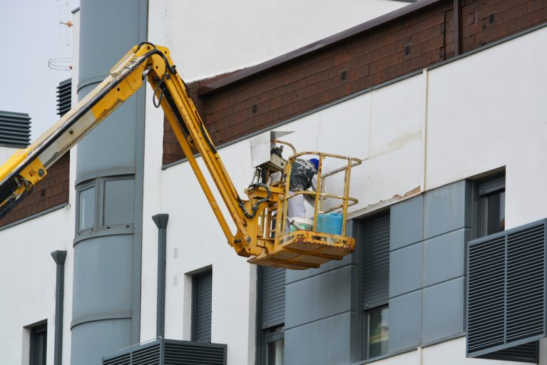 A man in a cherry picker repairing a building, symbolising professional maintenance.