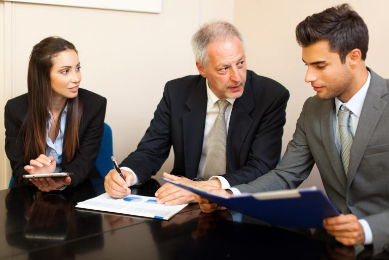 Three people in suits reviewing business reports, symbolising residential management.